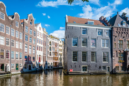dutch canal house: Amsterdam, Netherlands - August 1, 2016: Amsterdam cityscape, canal houses in Red Light District a blue sky day