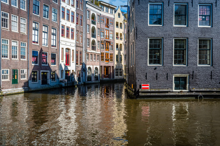 canal houses: Amsterdam, Netherlands - August 1, 2016: Amsterdam cityscape, canal houses in Red Light District a blue sky day