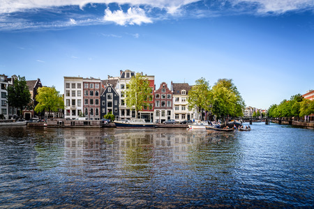 canal houses: Amsterdam, Netherlands - August 1, 2016: Amsterdan cityscape with beautiful canal houses reflected on water a blue sky day Editorial