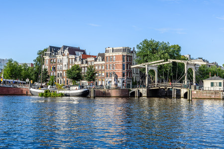 Amsterdam, Netherlands - August 1, 2016: Amsterdan cityscape with beautiful canal houses and bridge a blue sky day