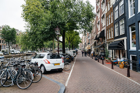 dutch canal house: Amsterdam, Netherlands - August 2, 2016: Street in historical city center of Amsterdam. It is one of the most romantic and beautiful cities in Europe.  Amsterdam is also a city of tolerance and diversity.
