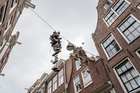 Amsterdam, Netherlands - August 2, 2016: Hanging shoes in a street in historical city center of Amsterdam. It is one of the most romantic and beautiful cities in Europe.  Amsterdam is also a city of tolerance and diversity.