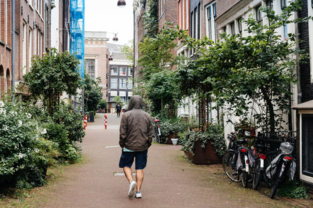 dutch canal house: Amsterdam, Netherlands - August 2, 2016: Man looking at the canal in Amsterdam city center. It is one of the most romantic and beautiful cities in Europe.  Amsterdam is also a city of tolerance and diversity.
