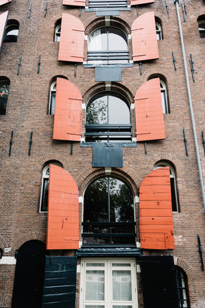 canal house: Amsterdam, Netherlands - August 2, 2016: Canal house with wooden shutters in Amsterdam. It is one of the most romantic and beautiful cities in Europe.  Amsterdam is also a city of tolerance and diversity.