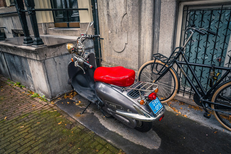 dutch canal house: Amsterdam, Netherlands - August 2, 2016: Scooter in the street in historical city center of Amsterdam. It is one of the most romantic and beautiful cities in Europe.  Amsterdam is also a city of tolerance and diversity.
