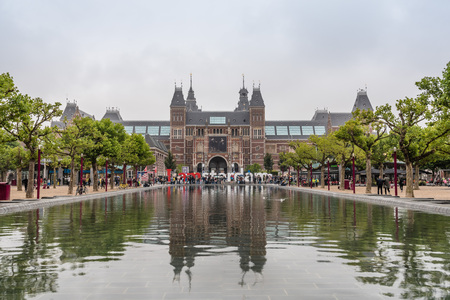 Amsterdam, Netherlands - August 2, 2016: Rjksmuseum in Amsterdam and reflections on pond a cloudy day. It´s a Dutch national museum dedicated to arts and history. It includes masterpieces by Rembrandt, Hals and Vermeer. Editorial