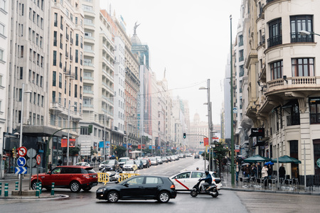 Madrid, Spain - November 20, 2016: Rainy day in Gran Via in Madrid. It is an ornate and upscale shopping street located in central Madrid. It is known as the Spanish Broadway.