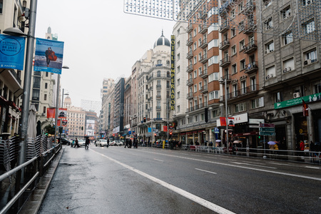 upscale: Madrid, Spain - November 20, 2016: Rainy day in Gran Via in Madrid. It is an ornate and upscale shopping street located in central Madrid. It is known as the Spanish Broadway.