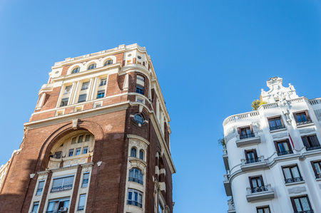 Madrid, Spain - September 18, 2016:   Low angle view of buildings at Gran Via Street in Madrid. It is an important street in Central Madrid with shops and theaters.