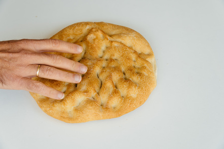 artisan bakery: Man hand on loaf of bread on white table, food closeup. Top view Stock Photo
