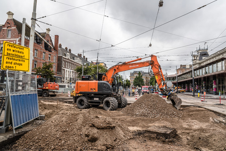 Amsterdam, Netherlands - August 3, 2016: Backhoe machine repairing the tram tracks in the streets of Amsterdam a cloudy and rainy day Stock Photo - 75517908