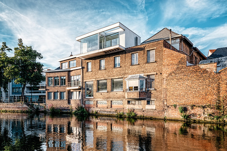 rehabilitated: Mechelen, Belgium - July 29, 2016: Cityscape of Mechelen with old rehabilitated buildings on the canal. Extension of an old building with modern architecture elements. Editorial