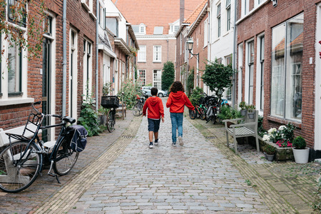 Haarlem, Netherlands - August 3, 2016: Kids walking in a picturesque street with beautiful traditional houses in Haarlem