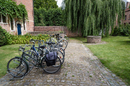 completely: Leuven, Belgium - July 30, 2016:  The Grand Beguinage of Leuven, is a well preserved and completely restored historical quarter is owned by the University of Leuven and used as a campus. Bicycles parked Editorial