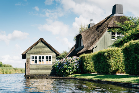 punter: Giethoorn, Netherlands - August 5, 2016: The village Giethoorn is unique in the Netherlands because of its bridges, waterways and typical boats calle punters.  It is also called the Venice of Holland