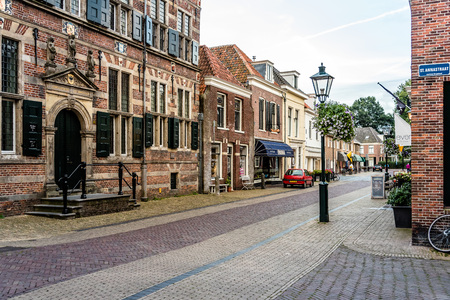developed: Naarden, Netherlands - August 5, 2016: Picturesque street in Naarden city centre. Naarden was developed into a fortified garrison town with a textile industry. It is an example of a star fort, complete with fortified walls and a moat.