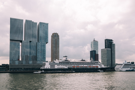 oma: Rotterdam, Netherlands - August 6, 2016: Cruises with skyscrapers at background in the harbor of Rotterdam Editorial