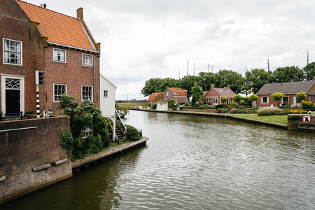 Enkhuizen, Netherlands - August 5, 2016: Old harbour of Enkhuizen a cloudy day . At the peak of its power Enkhuizen was one of the most important harbour cities in the Netherlands Editorial