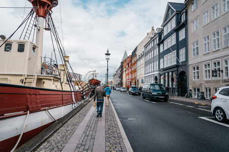 Copenhagen, Denmark - August 11, 2016: Nyhavn a cloudy day. It´s a 17th-century waterfront, canal and entertainment district in Copenhagen lined by coloured  townhouses, it has many historical wooden ships.