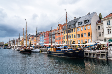 townhouses: Copenhagen, Denmark - August 11, 2016: Nyhavn a cloudy day. It´s a 17th-century waterfront, canal and entertainment district in Copenhagen lined by coloured  townhouses, it has many historical wooden ships.