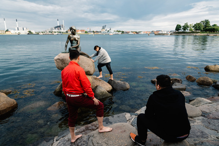 Copenhagen, Denmark - August 11, 2016: Some unidentified tourists trying to climb to little mermaid statue in Copenhagen, Denmark. Evening in summer