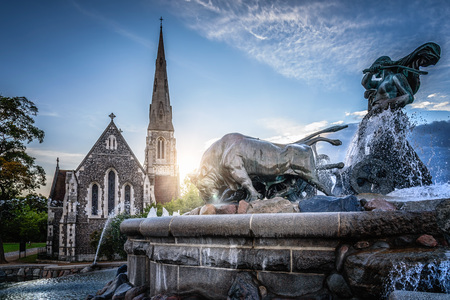 Copenhagen, Denmark - August 10, 2016. The Gefion Fountain is a large fountain in Copenhagen, view with church and sunlight on background. It is located in Langelinie Park is the largest monument in Copenhagen and used as a wishing well.