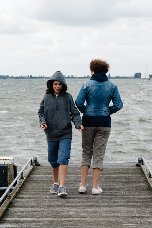 Woman and girl on wooden pier a cloudy summer day. The woman is standing back and the girl is walking to the camera. Concept  family