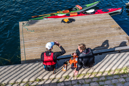 Copenhagen, Denmark - August 11, 2016: Canoeists resting after exercise and drinking beer sitting on waterfront of Copenhagen in a sunny summer day.