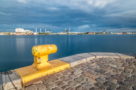 bollard: Scenic view of the skyline of Copenhagen at sunset from dock with yellow bollard on foreground Stock Photo
