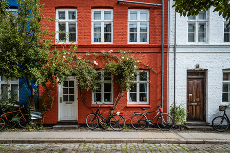 Copenhagen, Denmark - August 12, 2016. Picturesque old brick colorful houses in historical city centre of Copenhagen a cloudy day of summer, with bicycles parked