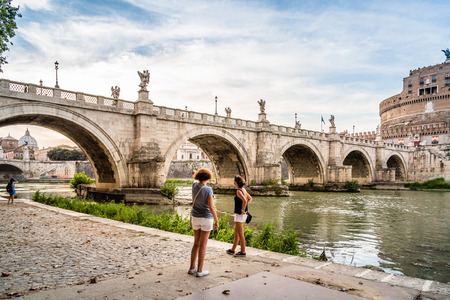 tiber: Rome, Italy - August 18, 2016:  Bridge and Mausoleum Castel Sant Angelo at sunset. The Mausoleum of Hadrian, usually known as Castel SantAngelo is a towering cylindrical building in Rome Editorial