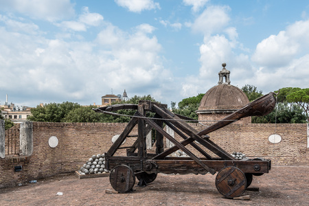 Rome, Italy - August 19, 2016:  Old roman catapult in Castel Sant Angelo a cloudy summer day. The Mausoleum of Hadrian, usually known as Castel SantAngelo is a towering cylindrical building in Rome