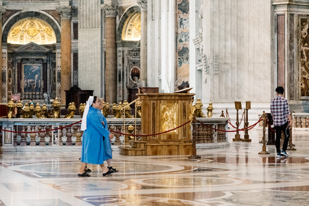 st: Rome, Italy - August 19, 2016: Nuns in the interior of St Peters Basilica. The Papal Basilica of St. Peter in the Vatican is an Italian Renaissance church in Vatican City, the papal enclave within the city of Rome.