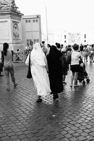 st: Rome, Italy - August 19, 2016: Two nuns walking on St Peters Square. Black and white picture. The Square is located directly in front of St. Peters Basilica in the Vatican City and was designed by Bernini