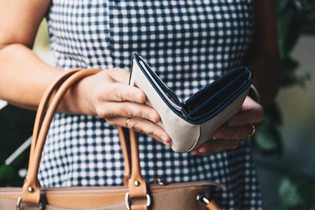 Close-upfoto van modieuze vrouw die de portefeuille uit handtas neemt.