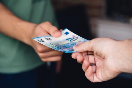 女性の手は、若い男にユーロのお金を与えています。