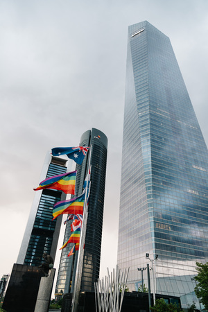 Low angle view of  business district with flags waving on foregr