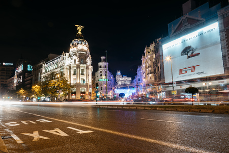 Madrid, Spain - December 8, 2017: Gran Via and Alcala streets in Madrid at night on Christmas time. Long exposure shot with light trails of traffic and blurred people