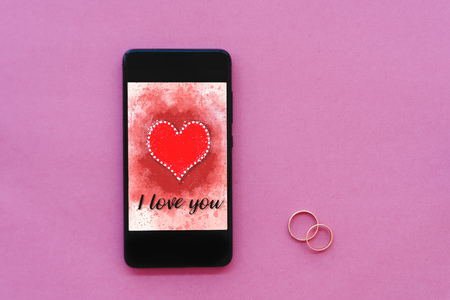 Valentines day sale background with heart illustration with the words I Love You on smartphone screen mockup on pink background with two wedding rings. View from above, flat lay