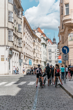 Prague,  Czech Republic - August 20, 2017: Cyclists in cobblestoned street in historical city centre of Prague