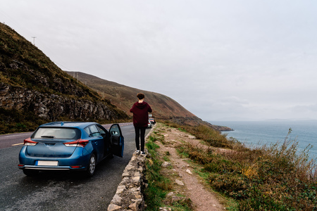 Woman stands on stone fence in scenic irish road Stock Photo