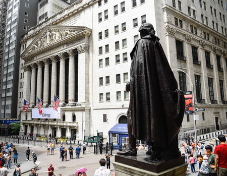 New York City, USA - June 20, 2018: Rear view of George Washington statue in Federal Hall against New York Stock Exchange building in Wall Street in Financial District