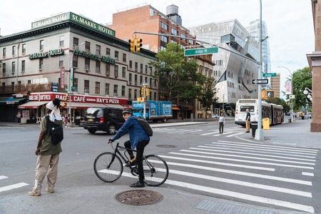Woman and cyclist are waiting for crossing street in New York 報道画像