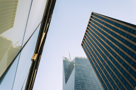 Low angle view of skyscrapers against blue sky in New York