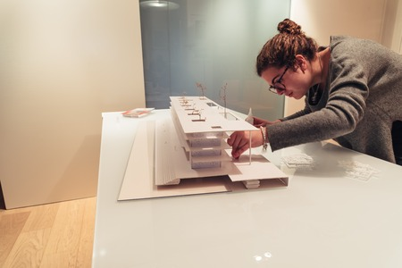 Female architect working on architecture model on table