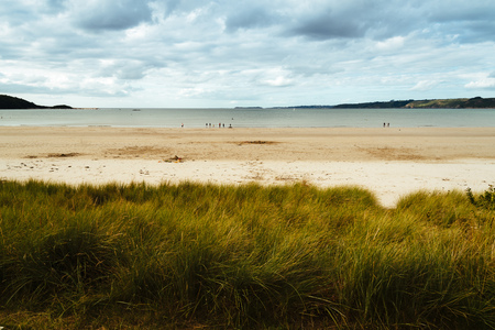 Tranquil beach against cloudy sky in Brittany