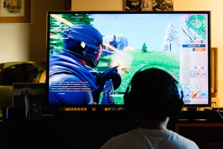 Teenager playing Fortnite video game with PlayStation on TV Redakční