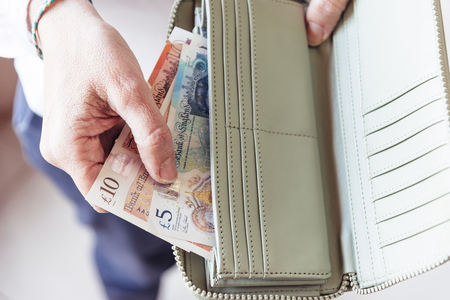 Woman taking out pounds from her pocket wallet