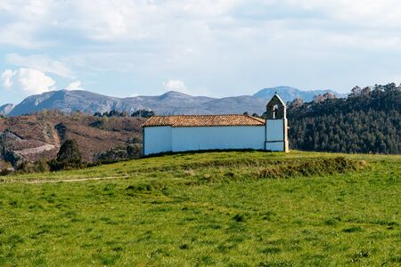 Small chapel in meadow against the mountains and blue sky, Asturias. Spain