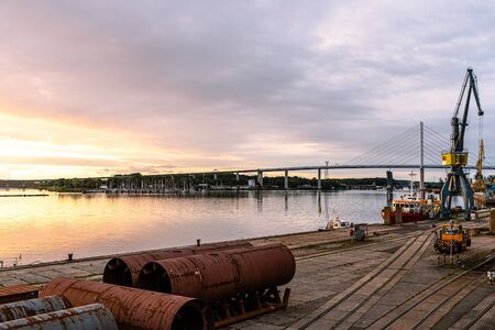 Panoramic view of the commercial harbour of Stralsund with cranes at sunrise against the bridge to the island of Rugen